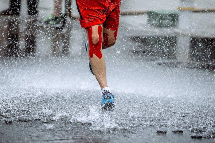 männlicher Athlet mit Klebeband auf den Knien
