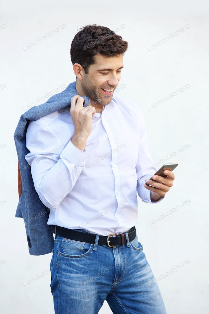 Young caucasian guy reading text message on cell phone against white background