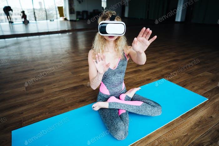 Frau im Yoga-Unterricht mit VR-Headset