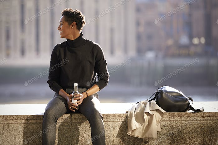 Young black woman wearing turtleneck sweater sitting in the sun on an embankment