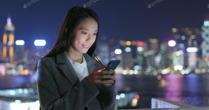 Frau Nutzung von Handy für online im Freien am Abend