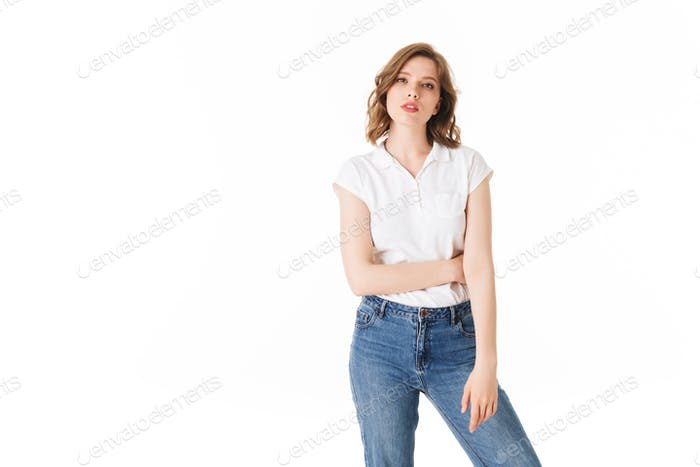 Portrait of young pensive lady standing in t shirt and jeans and thoughtfully looking in camera