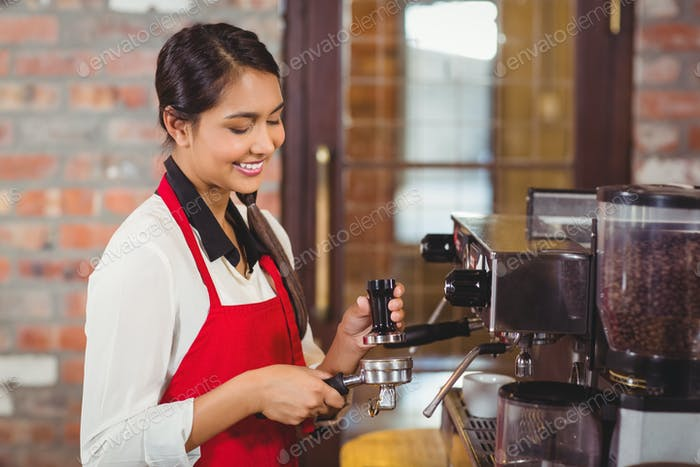 Pretty barista making a cup of coffee at the coffee shop