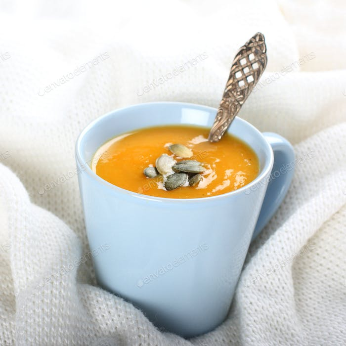 Blue cup of pumpkin soup on the knitted woolen fabric