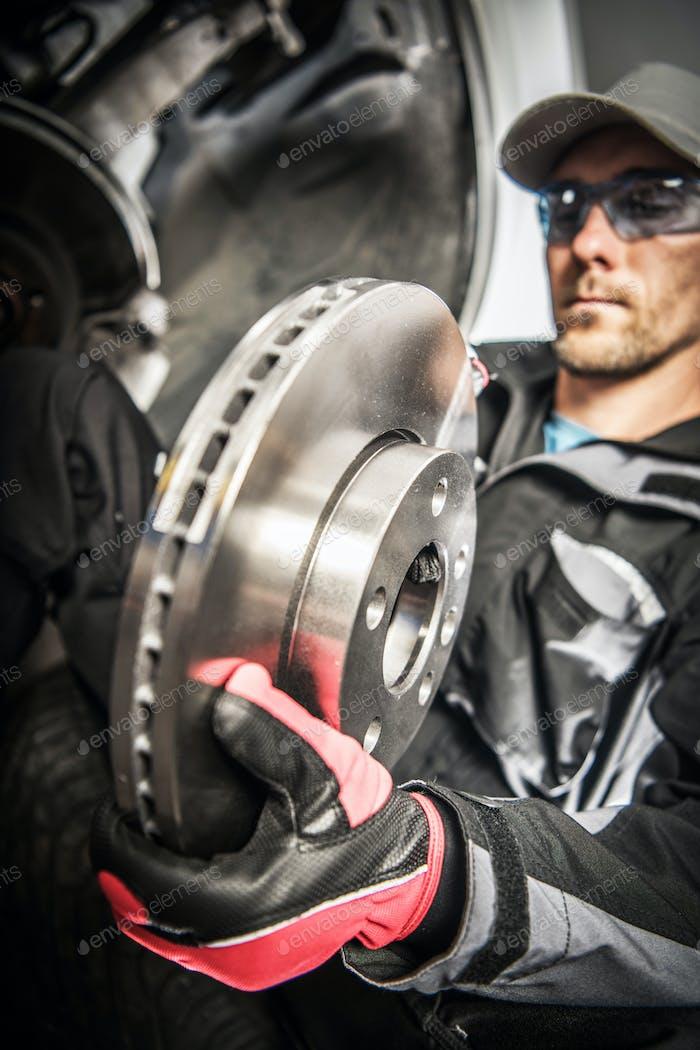 Car Mechanic Replacing Car Disc Brakes.