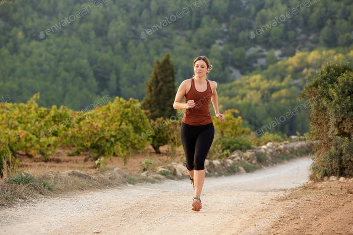 young sports woman running on dirt road