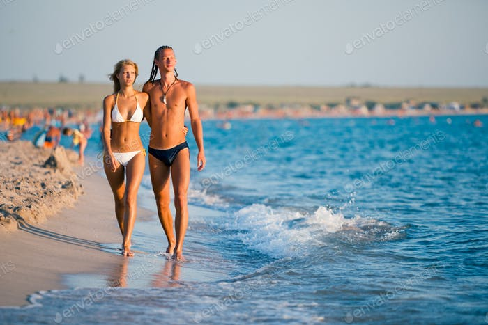 Beautiful young couple standing at sea water edge and enjoying sunshine