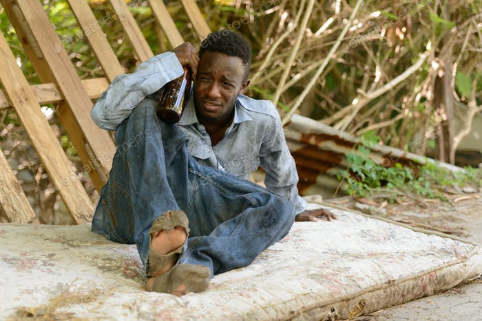 Sad young homeless African man getting drunk in the streets