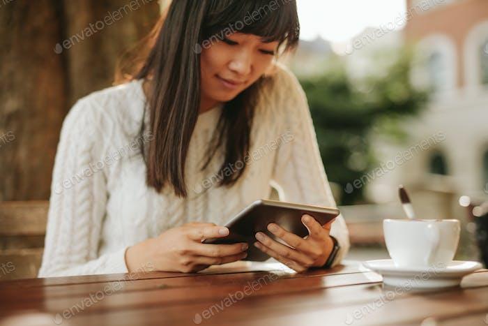 Chinesische Frau mit digitalen Tablette im Freien Café