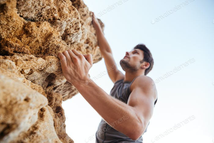 Young man climbing natural rocky wall