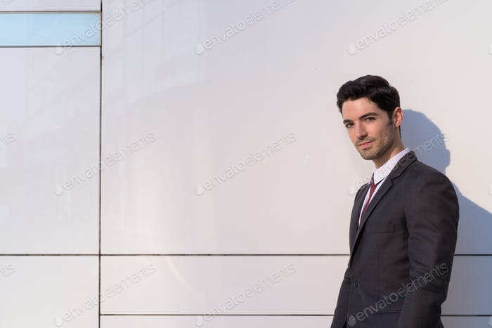 Portrait of young handsome businessman wearing suit in city