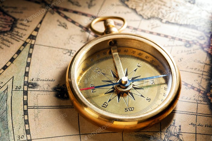 Antique compass on ancient map