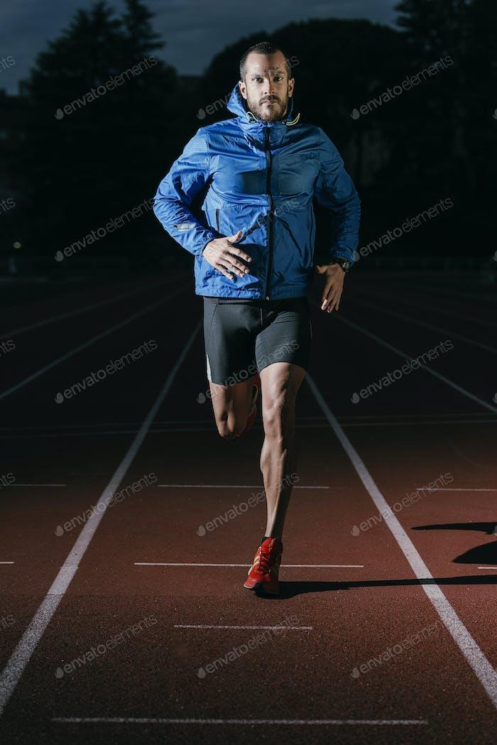 Attractive man Track Athlete Running On Track