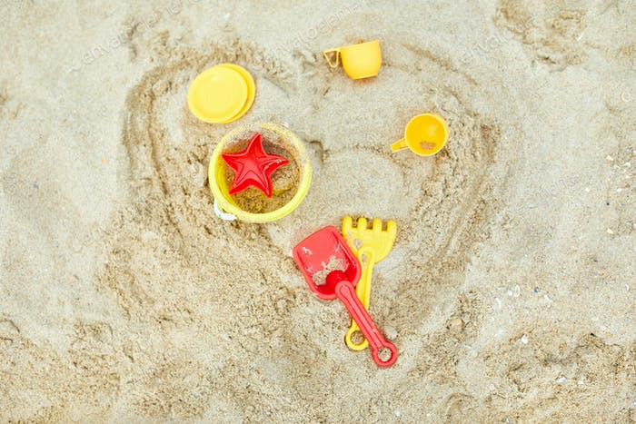 Top view, flat lay of  scattered plastic beach toys on sand background