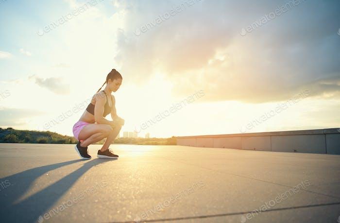 Female athlete squatting near ground outside