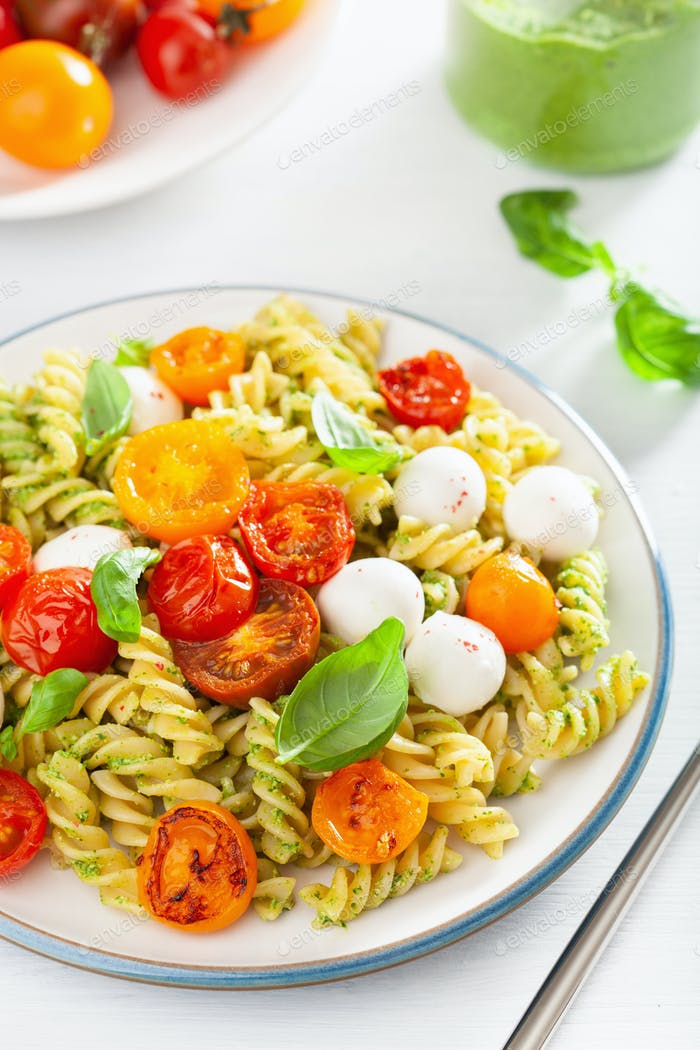 healthy fusilli pasta with pesto sauce, roasted tomatoes, mozzar