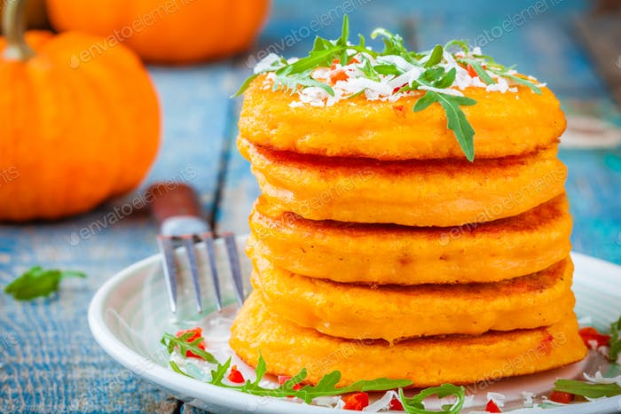 Pumpkin pancakes with chili pepper, parmesan cheese and rocket closeup
