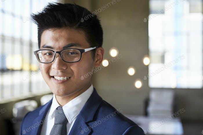 Junge asiatische Geschäftsmann lächelnd Kamera, Kopf und Schultern