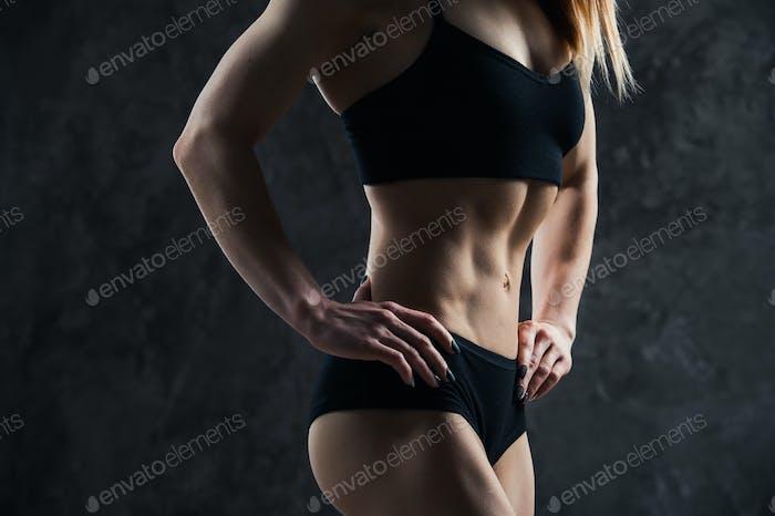 Sport sexy Mädchen mit großen Muskelbauch in einer schwarzen Sportbekleidung auf einem schwarzen Hintergrund.