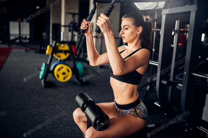 Female athlete trains on exercise machine in gym