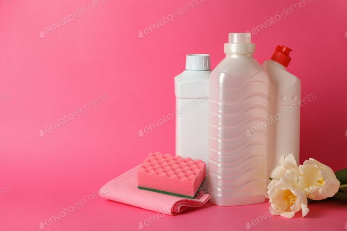 Cleaning tools and tulips on pink background