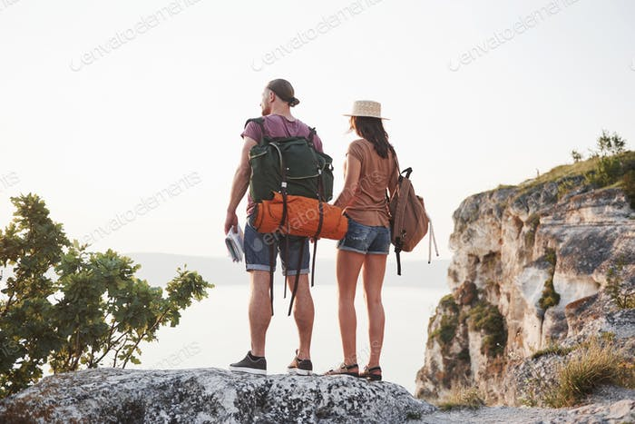 Two tourist male and woman with backpacks stand to the top of the crag and enjoying sunrise