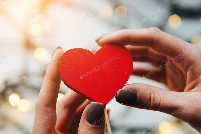 girl holding a red heart in the hands
