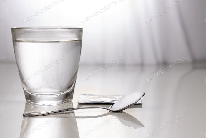 ORS or oral rehydration salt with glass of water, sachet and spoon