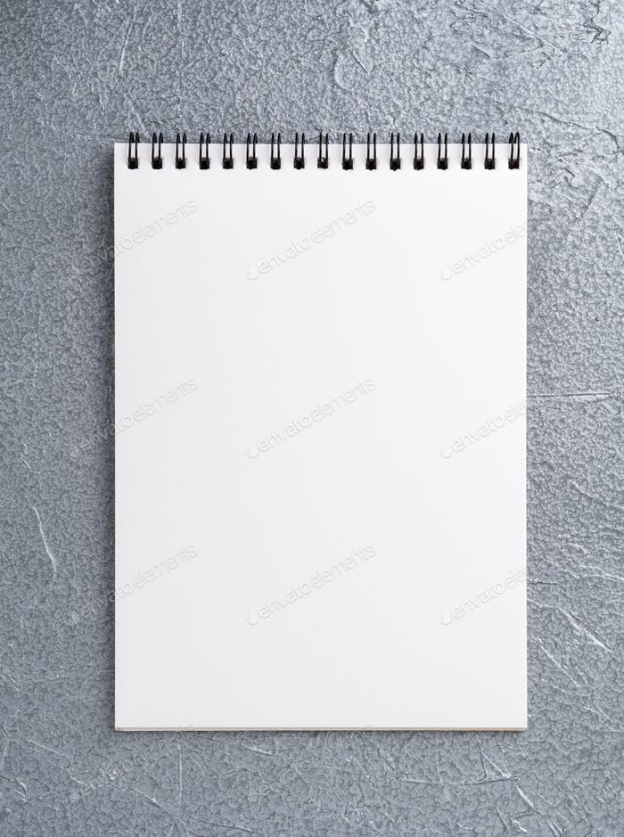 blank sheet of notebook with a spiral on a neutral gray textured silver metallic background