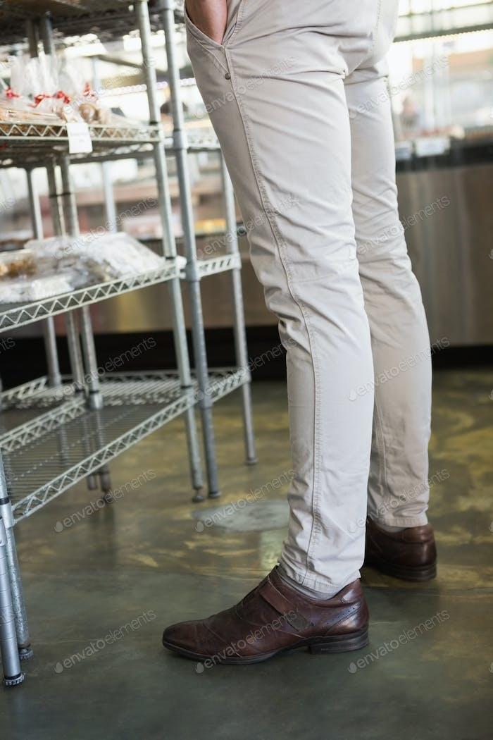 Stilvolle Beine des Mitarbeiters stehen an der Bäckerei