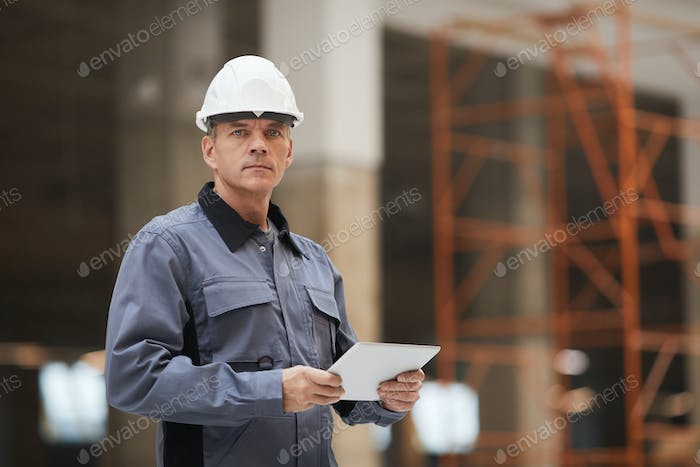 Mature Construction Worker Holding Tablet