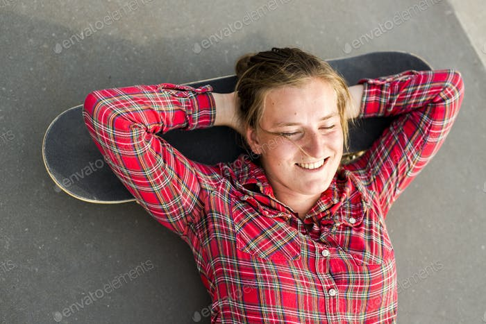 Directly above shot of happy woman lying her head on skateboard at skate park