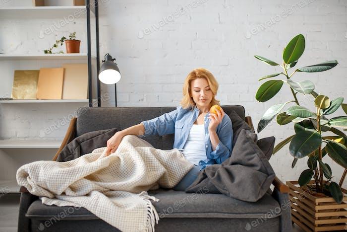 Mujer joven bajo un Libro de lectura manta en el sofá