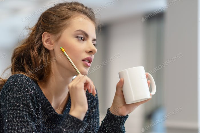 Thoughtful young woman making notes using notepad in kitchen.