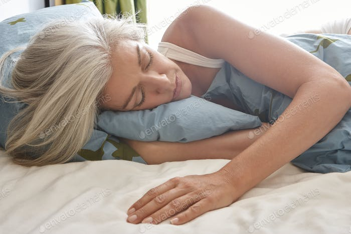 A mature Caucasian woman lying in bed sleeping