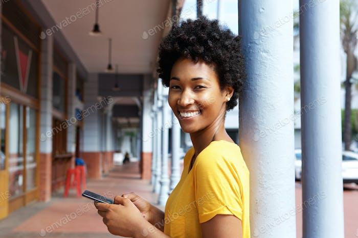 Attraktive junge afrikanische Frau hält ein Handy