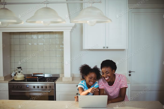 Mother and daughter using laptop in kitchen
