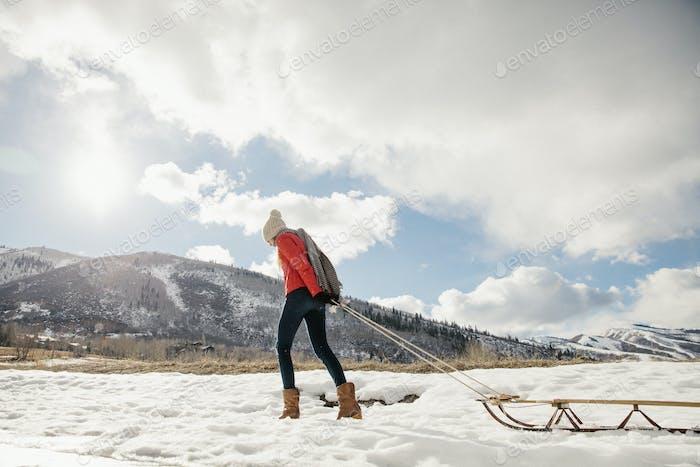 Ein junges Mädchen in einer roten Jacke zieht einen leeren Schlitten über den Schnee.