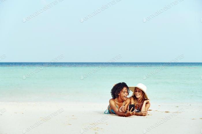 Freunde in Bikinis nehmen Selifes während Sonnenbräunung an einem Strand
