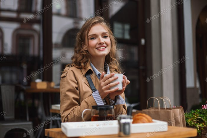 Young joyful woman in trench coat happily looking in camera hold