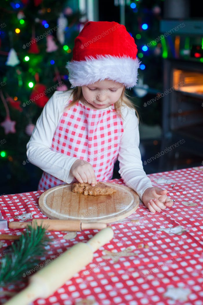 Adorable little girl eating the dough for ginger cookies in kitchen