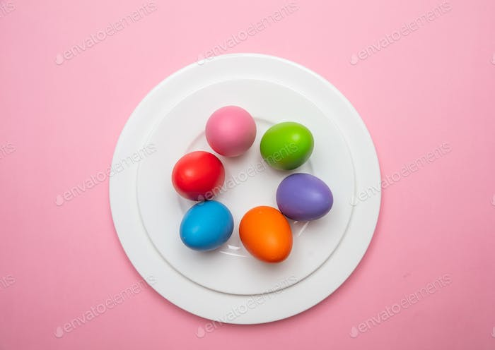 Easter eggs, pastel colors painted in a white plate, pink color background