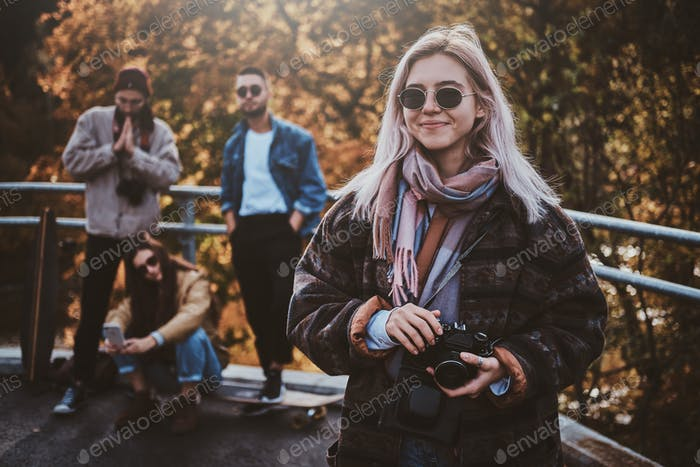 Beautiful blond girl and her friends at autumn park