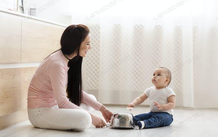 Kleiner Junge trommeln mit Mutter auf Metall Topf in Küche