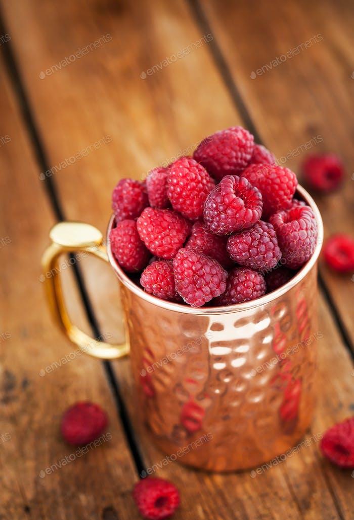 Fresh ripe raspberries in a copper mug