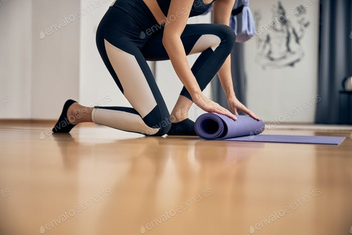 Slim woman rolling up yoga mat after session