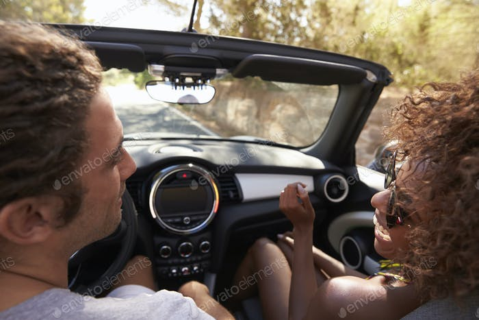 Happy young couple driving in open top car, woman clapping