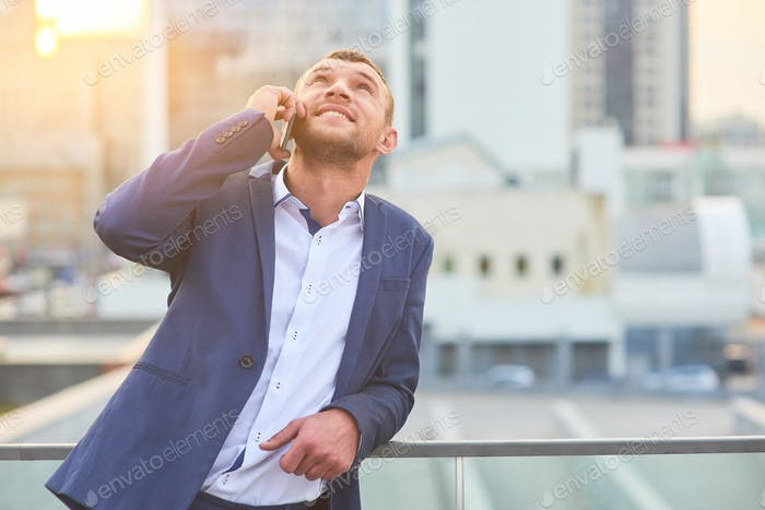 Businessman with phone looking up