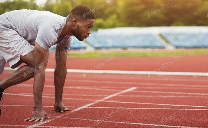 African-american male sportsman ready to run on stadium track