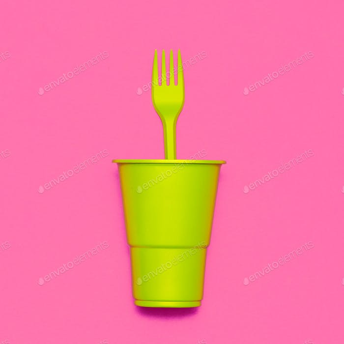 Plastic tableware. Minimal. Plastic cup and fork